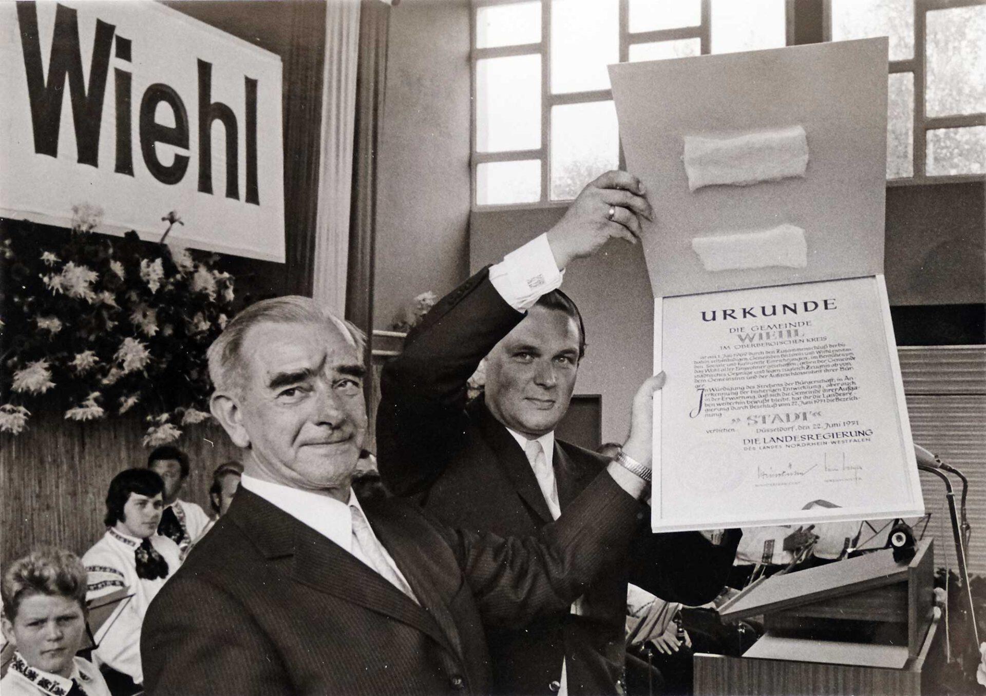 Stolz präsentieren beim Festakt am 21. August 1971 Bürgermeister Ernst Hardt (l.) und Stadtdirektor Horst Waffenschmidt die Urkunde zur Stadtwerdung